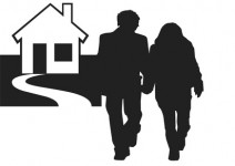 Couple holding hands with home in background