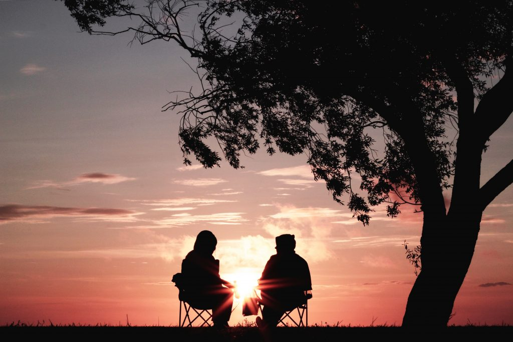 Image of couple sitting under tree at sunset theoretically discussing collaborative divorce and divorce mediation.